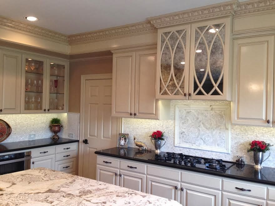 Like the curved lines in the glass doors and the white cabinets with the combination of contrasting colors on the granite/marble counter tops.