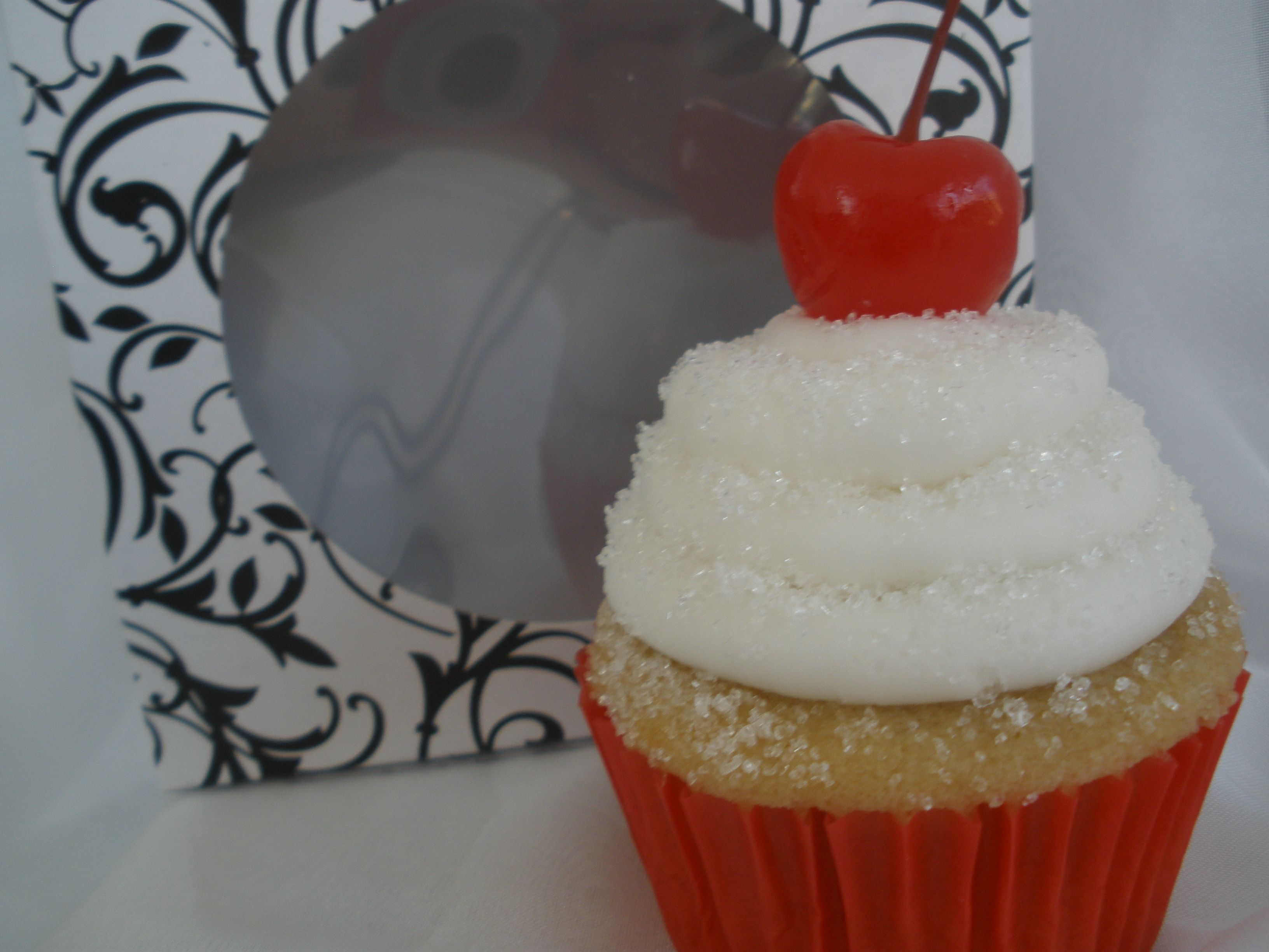 Vanilla Cupcake stuffed with a Hershey kiss and topped with vanilla buttercreme with sprinkled sugar and a cherry.