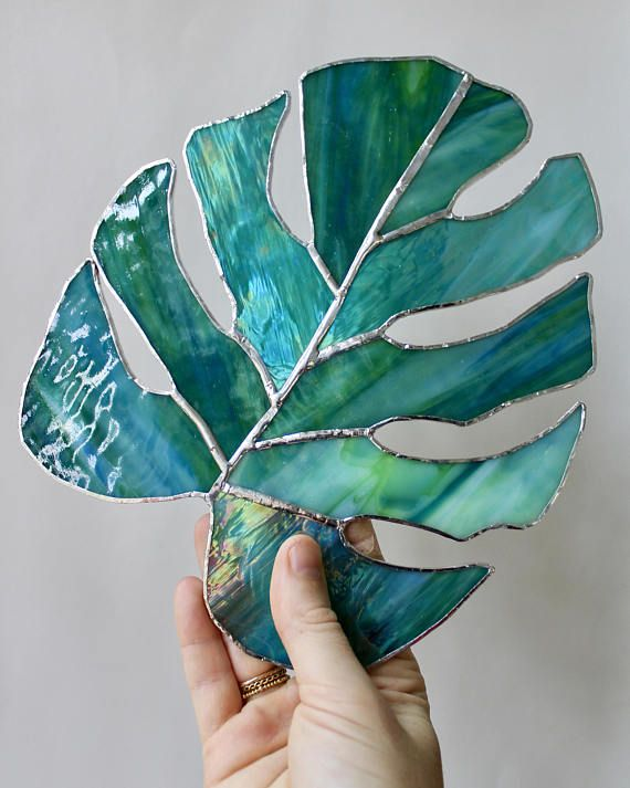 This listing is for the Stained Glass Sea Green Monstera Leaf All stained glass pieces are hand-crafted and created individually, so each piece will be completely unique. I use a lot of recycled stain glass from local artisans in my community, so by nature, each piece will also vary slightly in color and texture. To create this monstera leaf, I sketched out my design to create a hand-drawn stencil. Then, I cut the glass using hand tools, sand the edges down with a grinder, copper foiled…