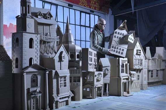 "Simon Costin's Dickensian street scene, commissioned by the Museum of London.    The cardboard city streetscape, complete with narrow alleys, church towers and shop fronts, is made entirely from cardboard and inspired by the descriptive essays of Charles Dickens. ""My intention [was] to create a fantasy vision of London as it would have been glimpsed by Dickens on his nocturnal wanderings through the city..."""