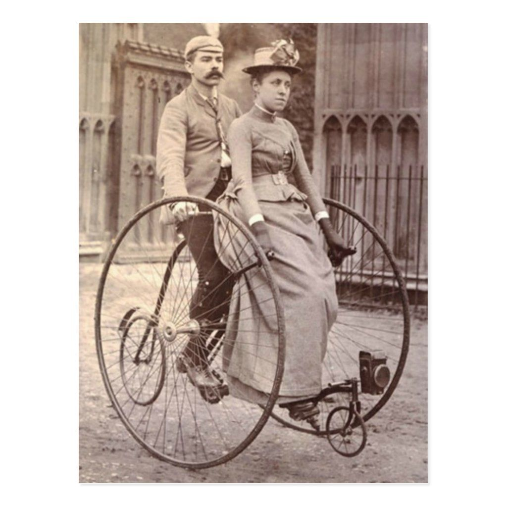 A vintage photograph of a Victorian couple on a tandem bicycle.