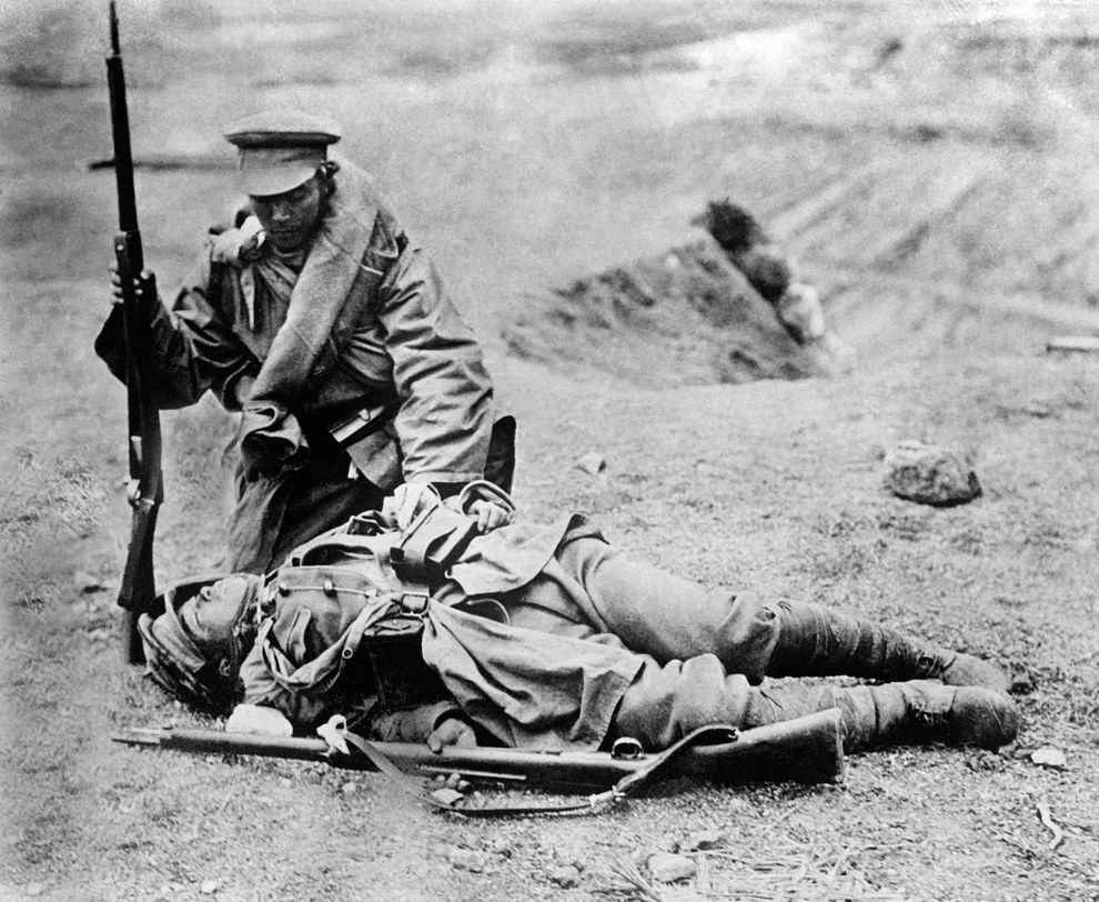A Japanese soldier attempts in vain to rouse his dead comrade ...