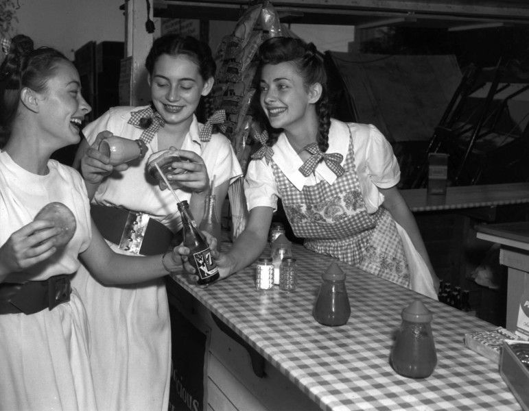 Three teenage girls at a Minnesota State Fair food counter with a 7-Up bottle and burger buns in 1947. Photo from the Collection of the Minnesota Historical Society, courtesy of the Minnesota State Fair.