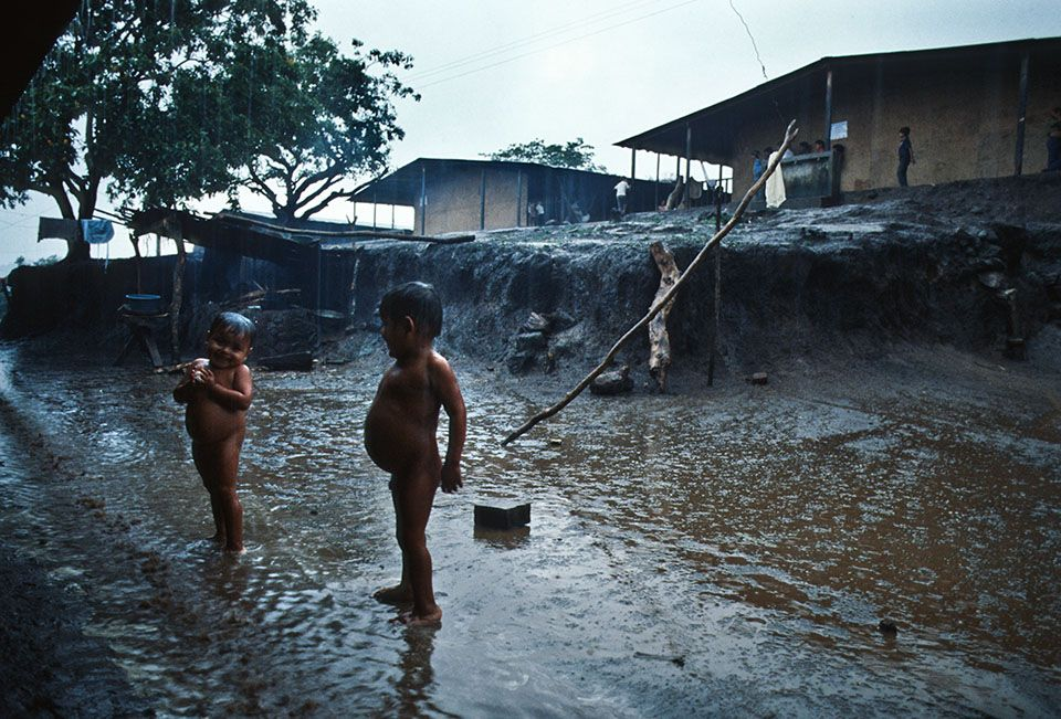 1985. Niños con sus vientres inflamados por las lombrices juegan bajo la lluvia en un campo de refugiados en el departamento de La Libertad.