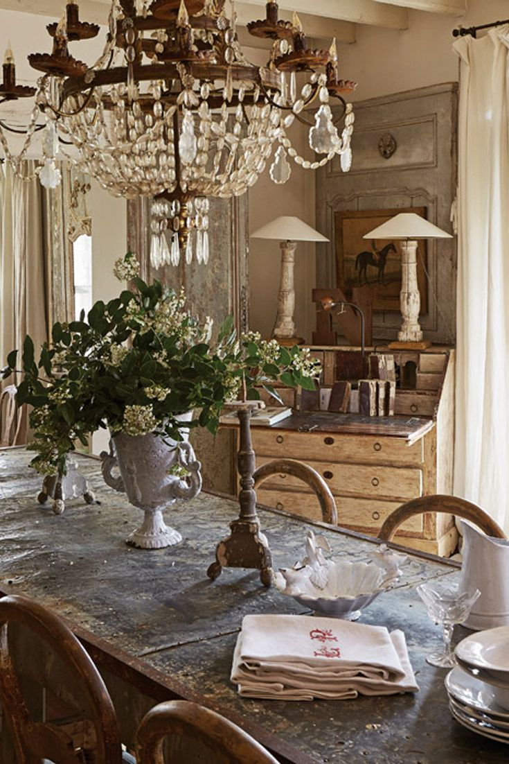 A crystal-and-wrought-iron chandelier from Southern France graces the farmhouse table in this charming abode outside of Paris, France. The furnishings bestow a serene balance of rusticity and elegance throughout the home.
