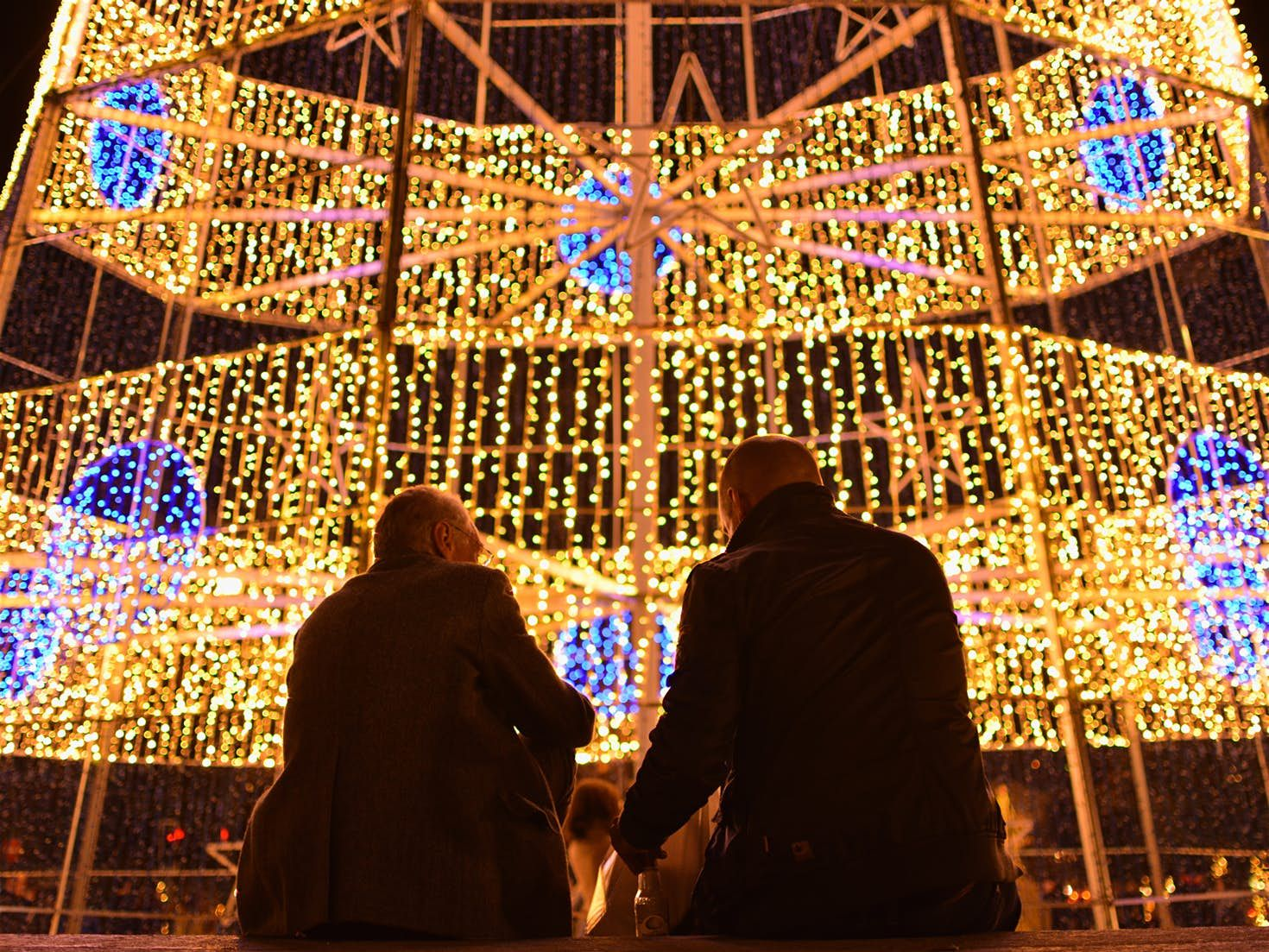 Two men sit in front of a Christmas tree made of lights in Porto, Portugal