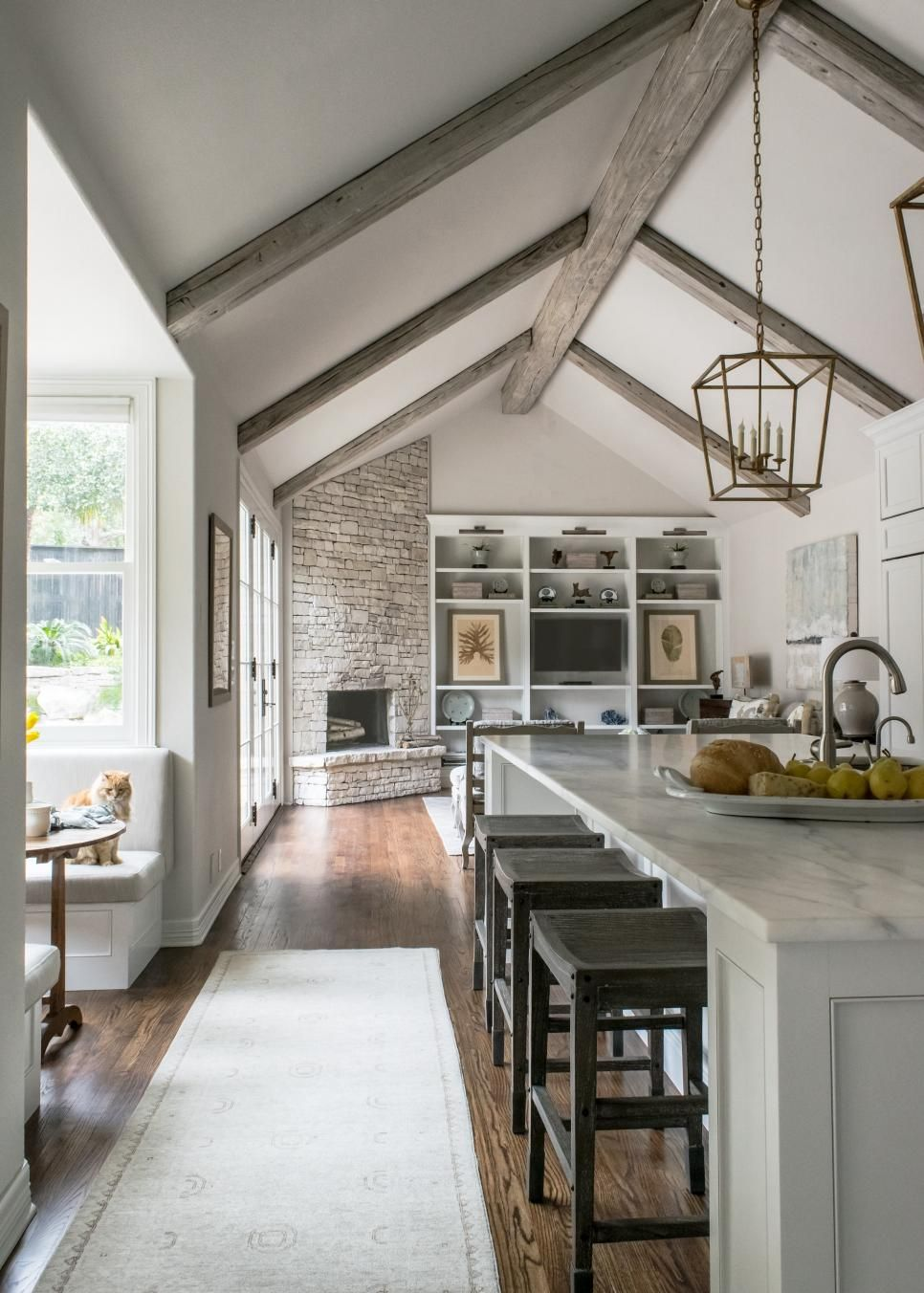 With Vaulted Ceilings Marble Surfaces And Crisp White Cabinetry This Contemporary Kitchen Remodeled Vaulted Ceiling Kitchen Contemporary Kitchen Remodel Home #vaulted #ceiling #wood #beams #living #room
