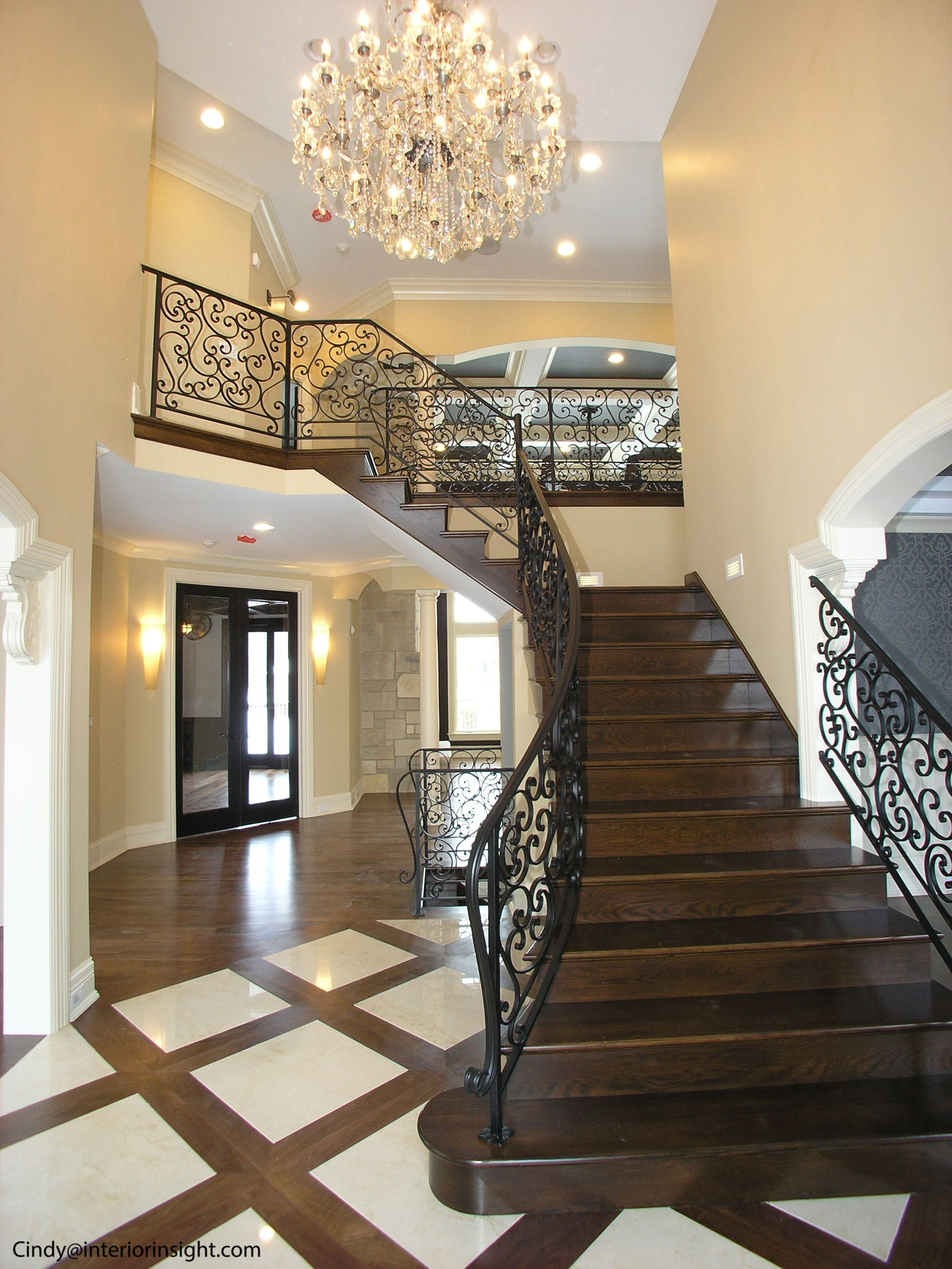 Double Foyer Lighting : Story foyer with curved iron railings and wooden