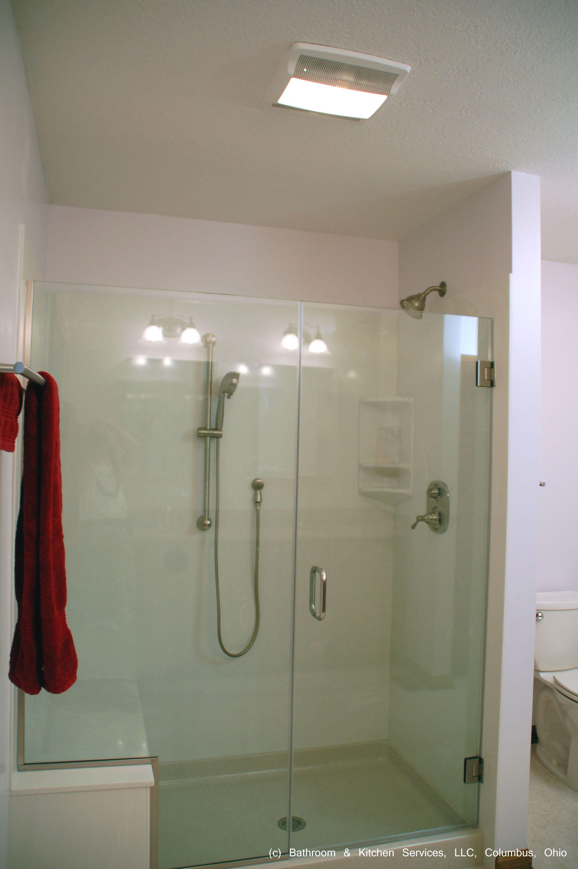 This large cultured marble shower surround with builtin seat and frameless glass shower is