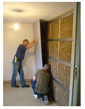 Two Men Installing A Studio Wall System By Fixing Acoustic Plasterboard To Resilient Bars On