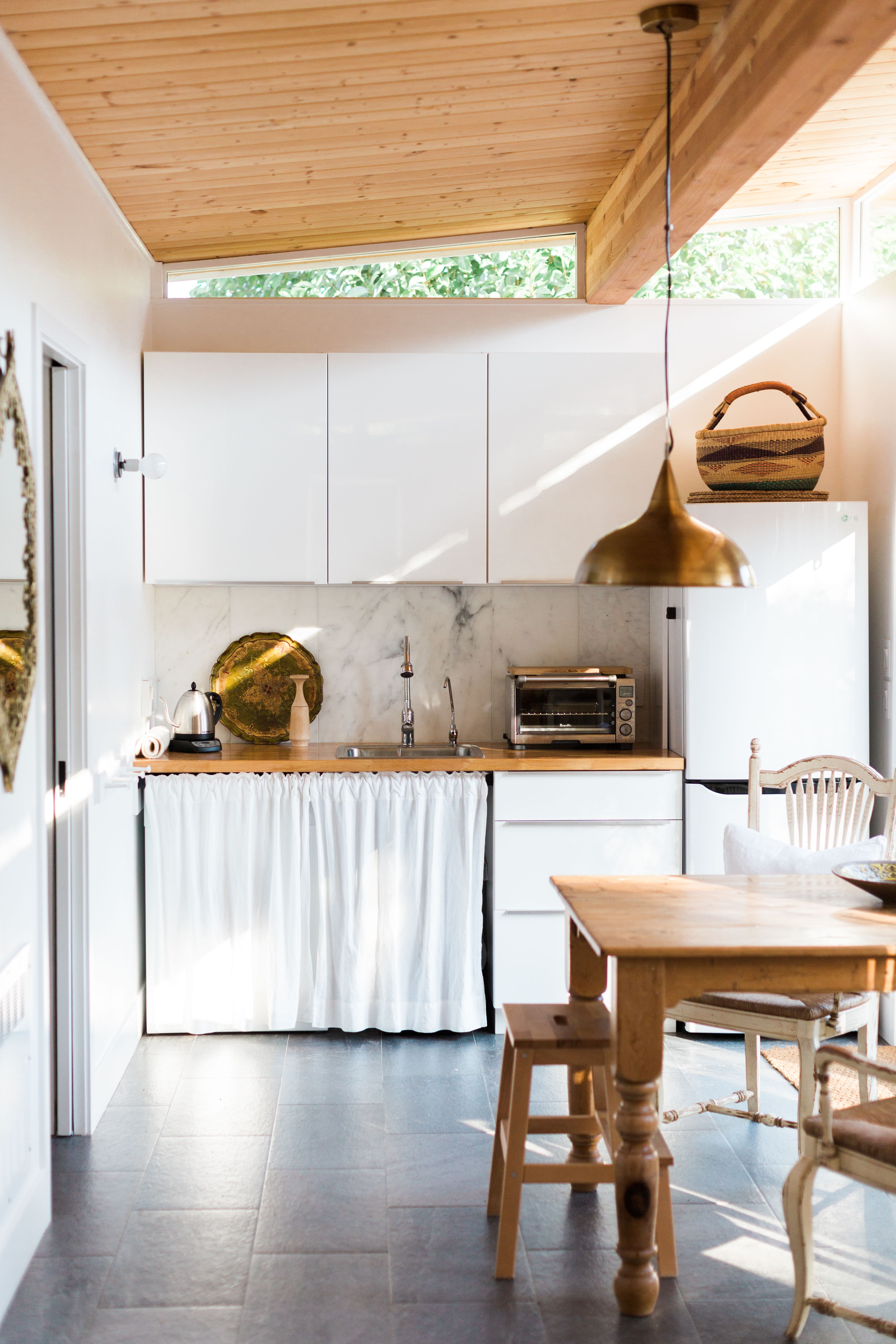 This tiny kitchen is beautiful, clean and functional.  The wall paint color is Benjamin Moore, Chantilly Lace Eggshell. (Chosen for its perfect match to the vinyl windows and happily turns out to be a great white that I would use again.)