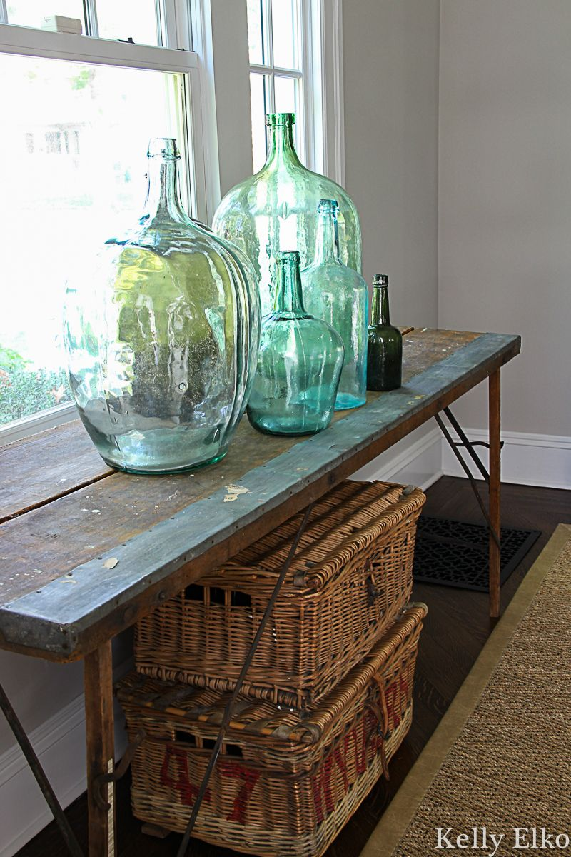 Beautiful collection of vintage demijohn bottles on an old wallpaper pasting table kellyelko.com #vintagedecor #antiquedecor #demijohn #rattan #antiques #falldecor #collections #vintagecollection #vintagedecor