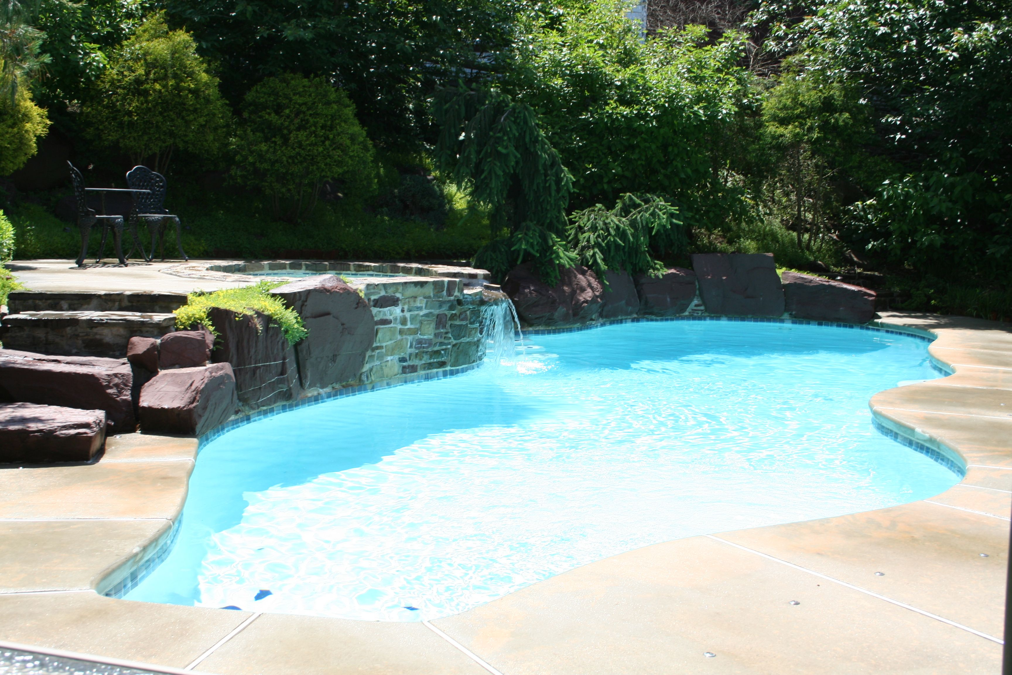 Free Form In Ground Plaster Pool White Plaster Broom Finished Concrete Natural Boulders Raised Spa Gunite Swimming Pool Construction Pool Pool Builders