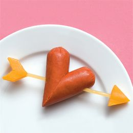 heart shaped hot dog with cheese and uncooked pasta arrow