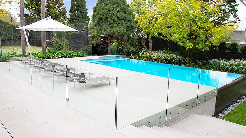 Pool and spa with blue interior tile and infinity edge. Glass pool fence fixed to outside of wall. Pinned to Pool Design by Darin Bradbury.