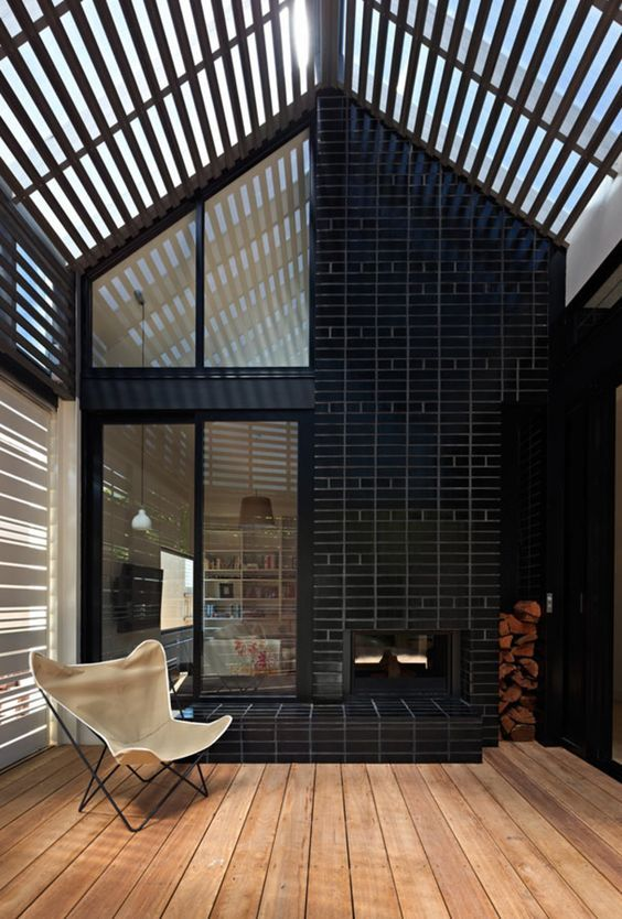 An interesting brick pattern and a double sided fireplace makes a feature of the covered deck area in House Reduction Cheminees Philippe indoor/outdoor double sided fireplace for warmth and ambience.