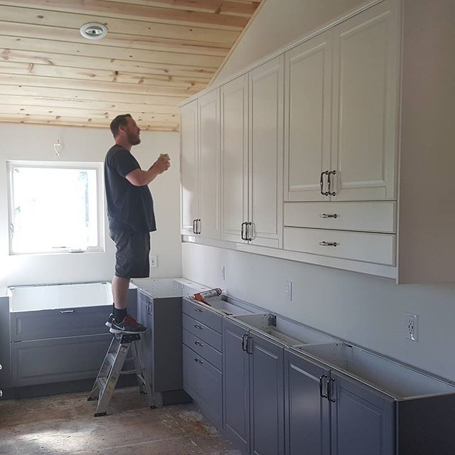 Putting the finishing touches on a Bodbyn white and gray kitchen