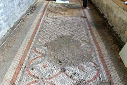 A photo of a stone tiled mosaic floor with a mud stain through it at Chedworth Roman Villa