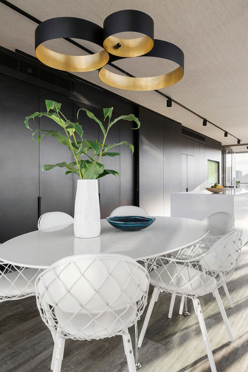 Black Pendant Lights Above A Round White Dining Table Perfectly Match The Black Wall Of Cabinetry And The White