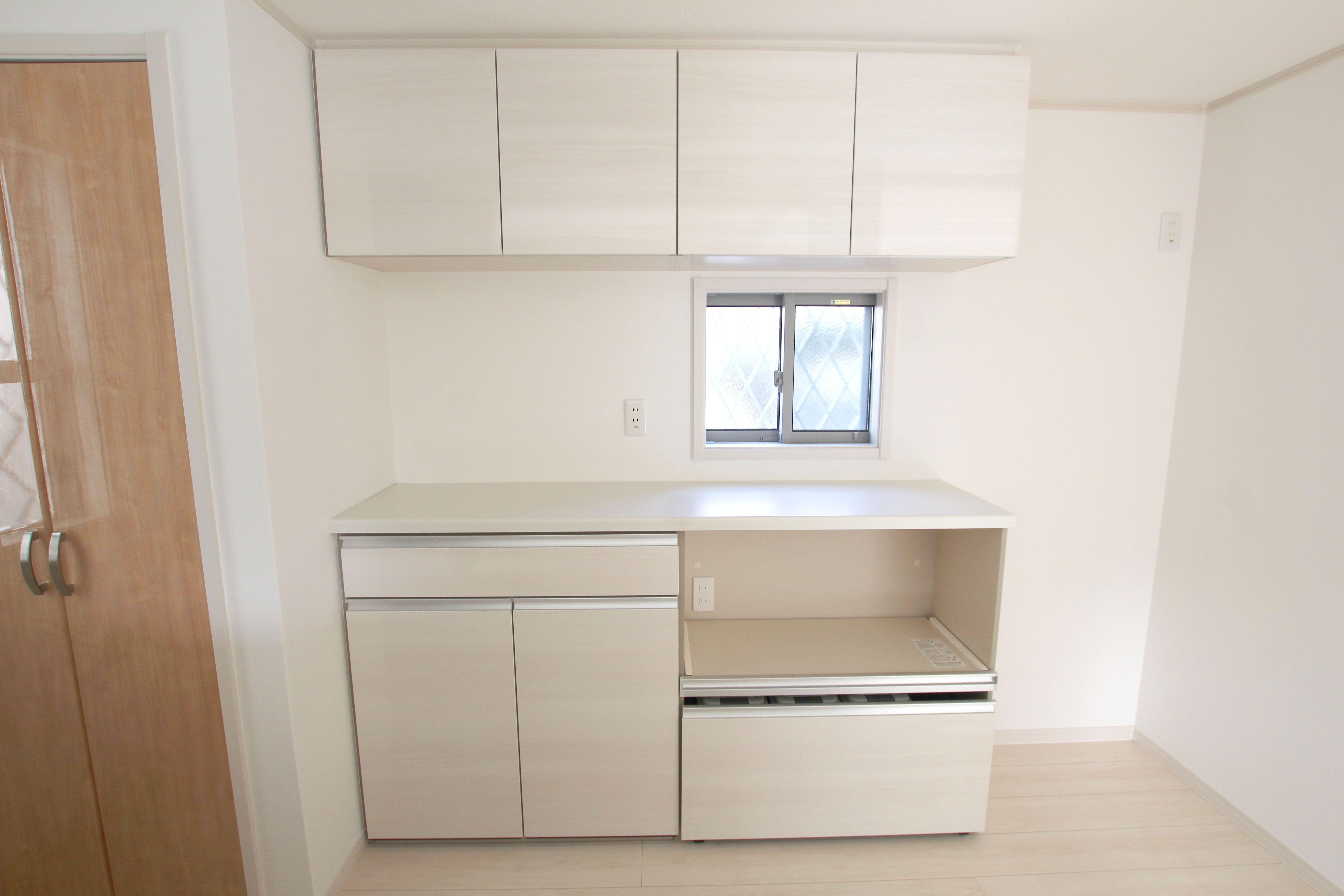 キッチン背面部に配されたカップボードと吊戸棚 大容量の収納が可能で