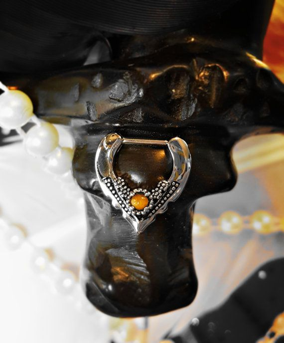 PLEASE READ REFUND/RETURN POLICY BELOW BEFORE YOU PURCHASE  This is a septum, daith, or rook clicker. Beautiful victorian style V or point in a silver surgical steel color setting with genuine tigers eye. Description: Septum Clicker (Lab Created Opal Center) Bar Width: Clicker Length 8mm 6mm Inner Diameter: 5/16 or 7mm Material Type: Surgical Steel 316L Gauge: 16g IF YOU HAVE AN ISSUE OR CONCERN with your jewelry or a lost package do not submit a request or open a case. First, contact me by…
