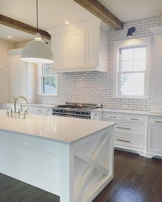 Kitchen with wood beams, white cabinets, subway tile, and hardwood flooring