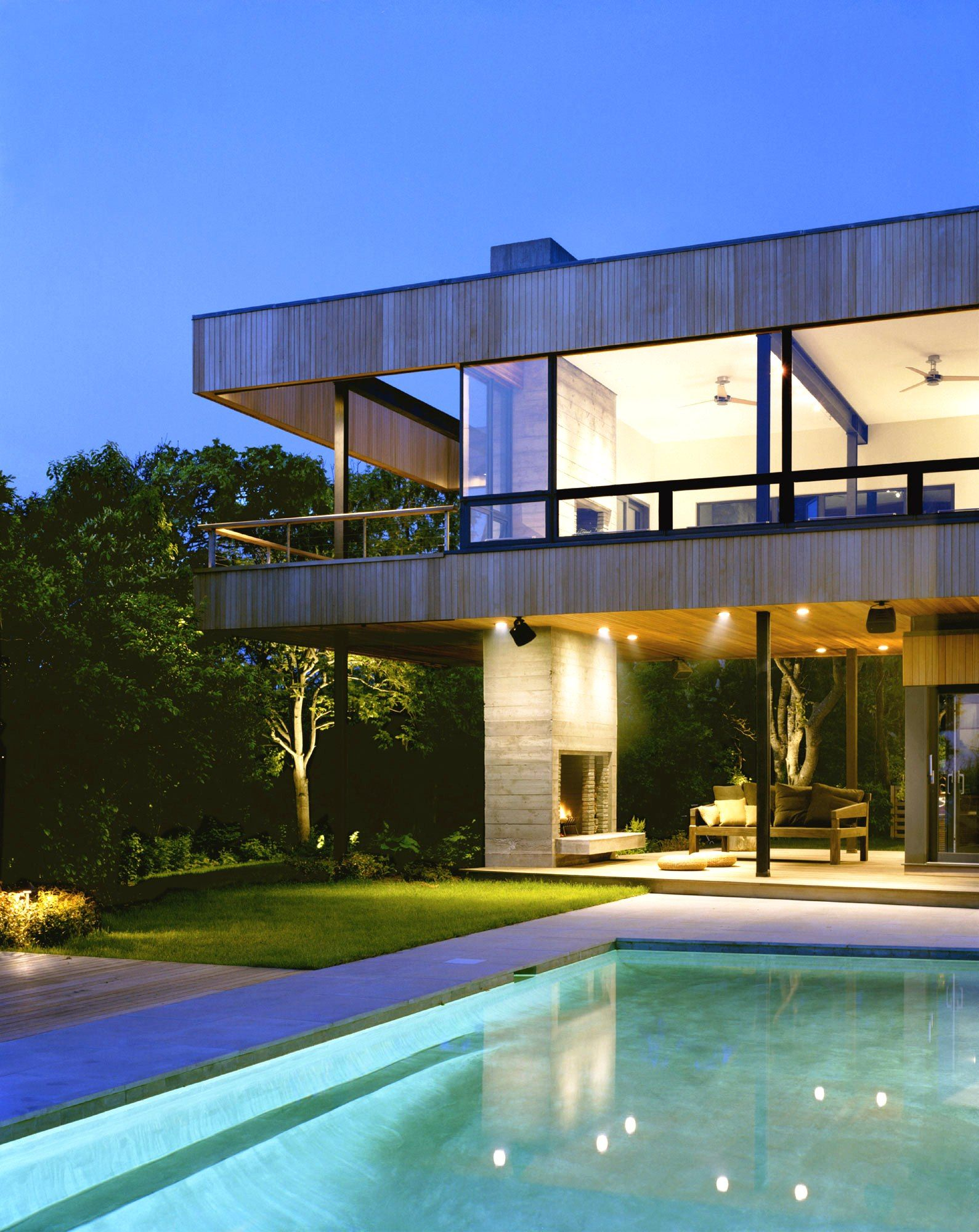 Exterior design excellent evening view of blue modern swimming pool design in minimalist house outdoor