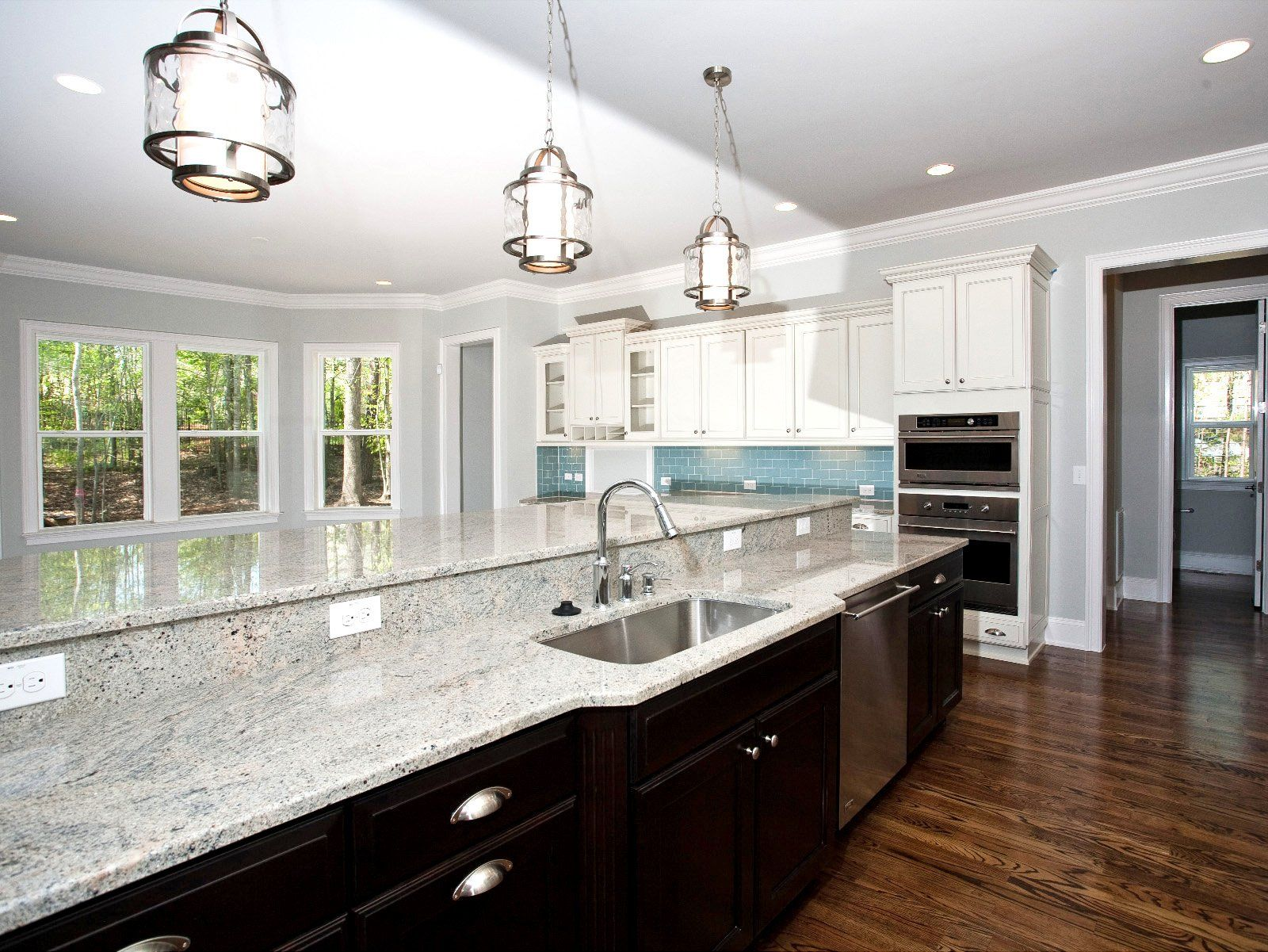 Black Cabinets Light Granite Countertops and a Blue Glass back