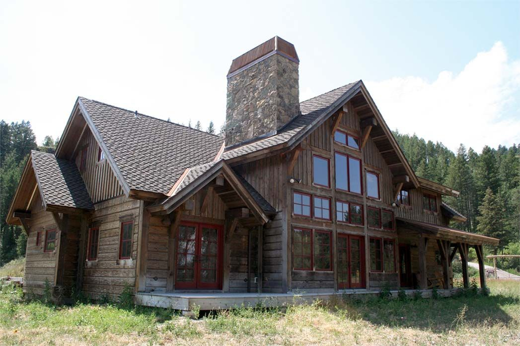 ordinary rustic timber frame homes #2: The Silver Springs is a rustic timber frame home design with a covered  porch accented with timber posts and arches and copper overhangs.