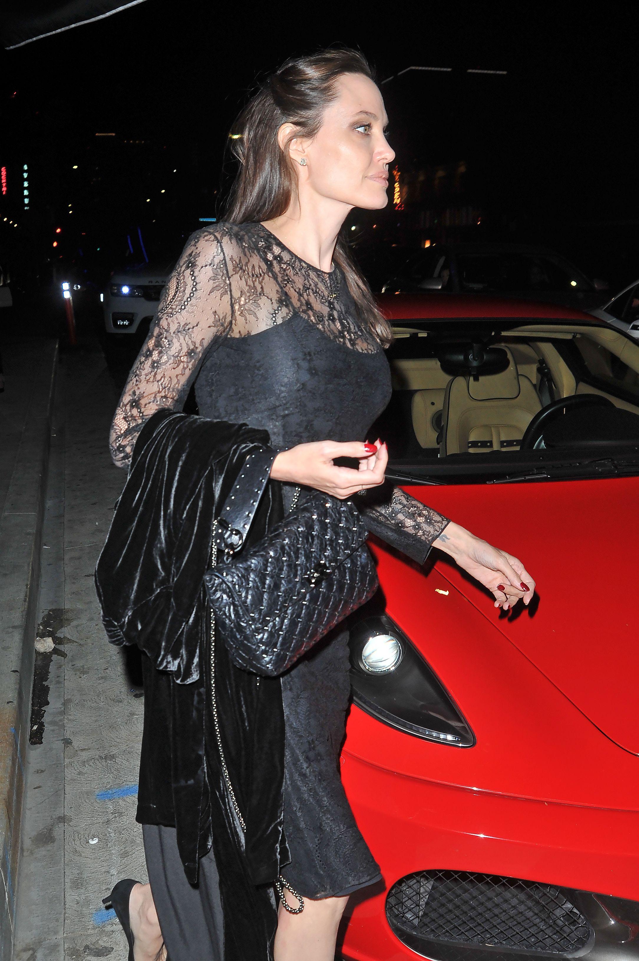 c5f89c2767a Bag goals! The iconic  AngelinaJolie captured in LA wearing the it  accessory of the season  Valentino Garavani Rockstud Spike in a dark shade.