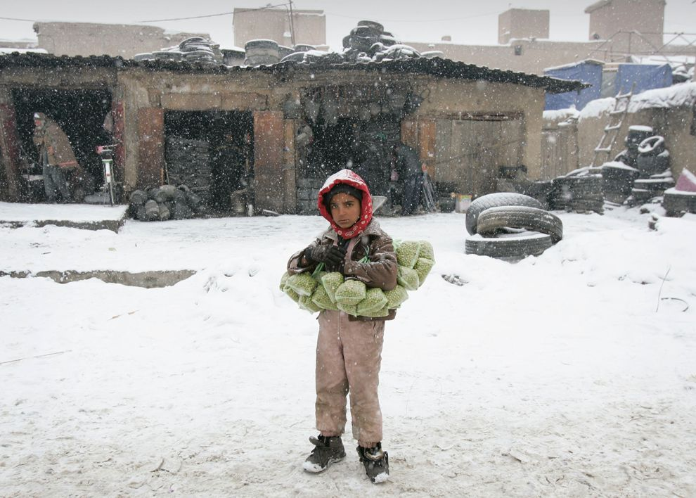 An Afghan boy selling packed peas, waits for customers on a cold and snow covered street in Kabul, Afghanistan, Feb. 19, 2012. (Ahmad Nazar/Associated Press) #