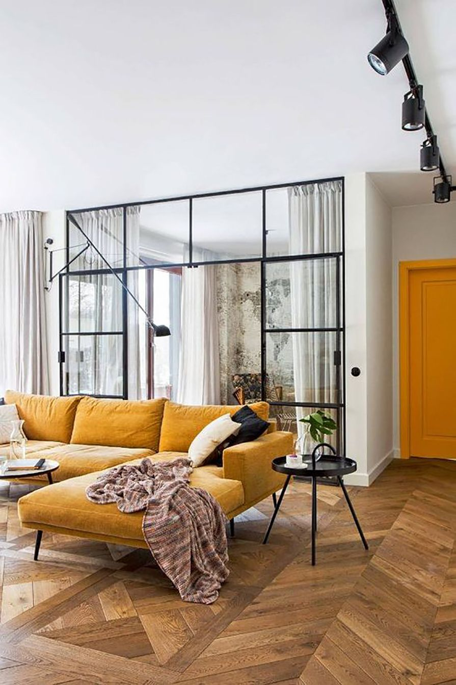 Fresh warm and inviting interior with natural light and striking contrast black window frames against wood floor and ochre colour sofa