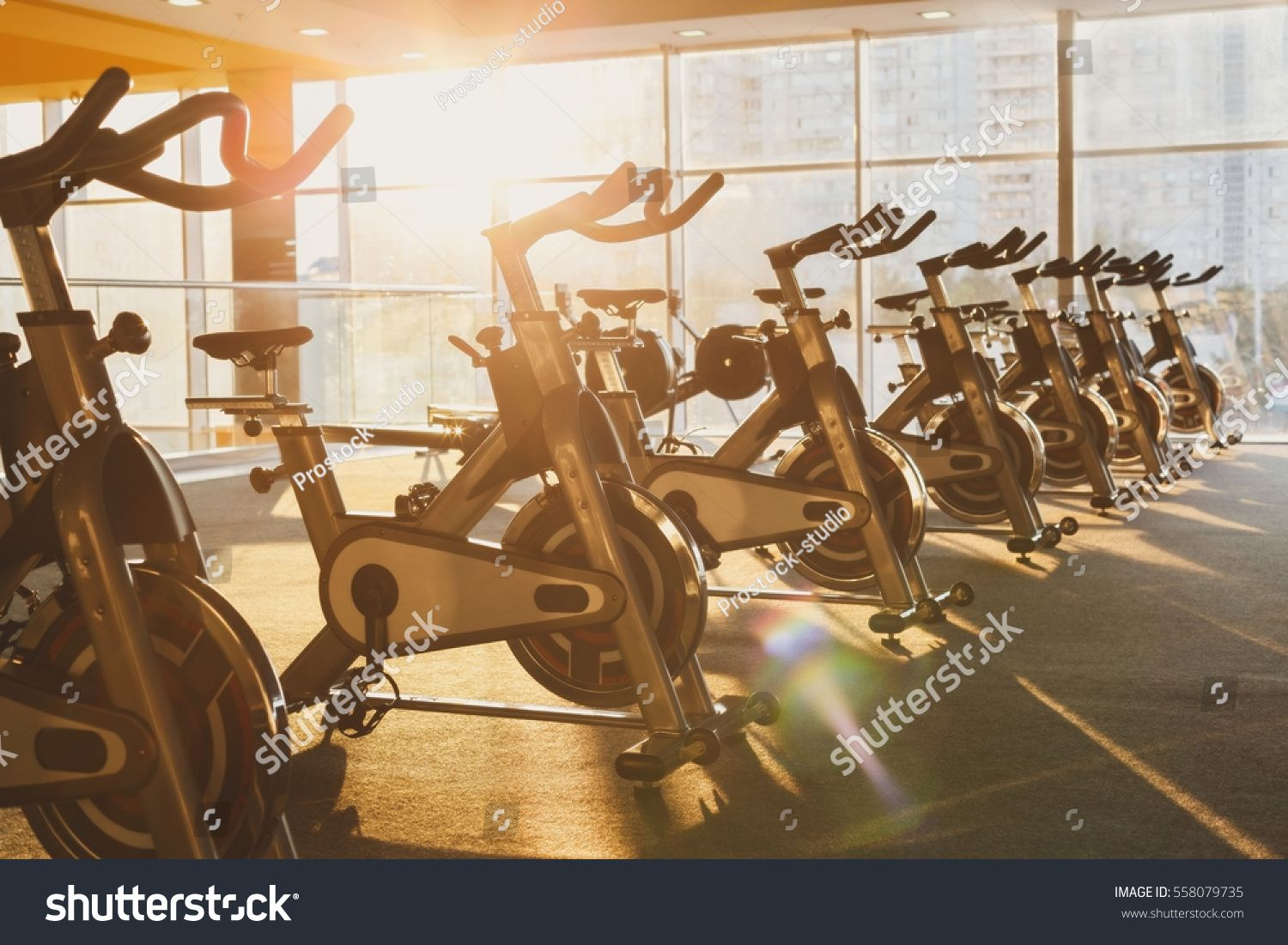 Modern gym interior with equipment. Fitness club with training exercise bikes in evening backlight....