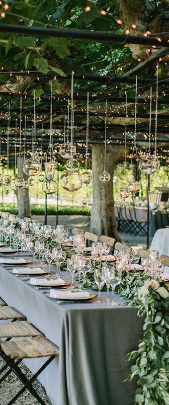 Guirlande over tafel van groen en bloemen en hangende deco ...