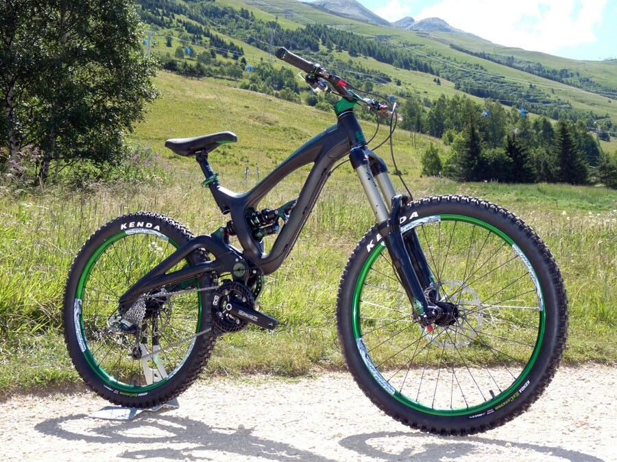 A Black Mountain Bike With Green Rims And Herbalife Stickers