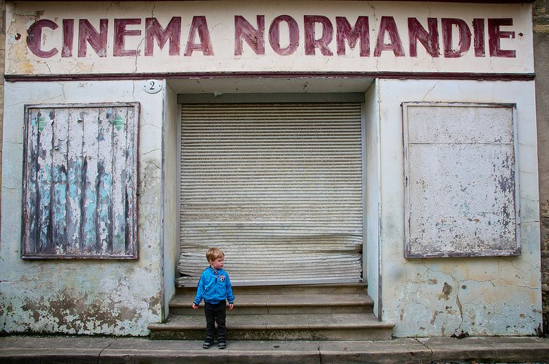 Boy In Front Of Old Movie Theater In France
