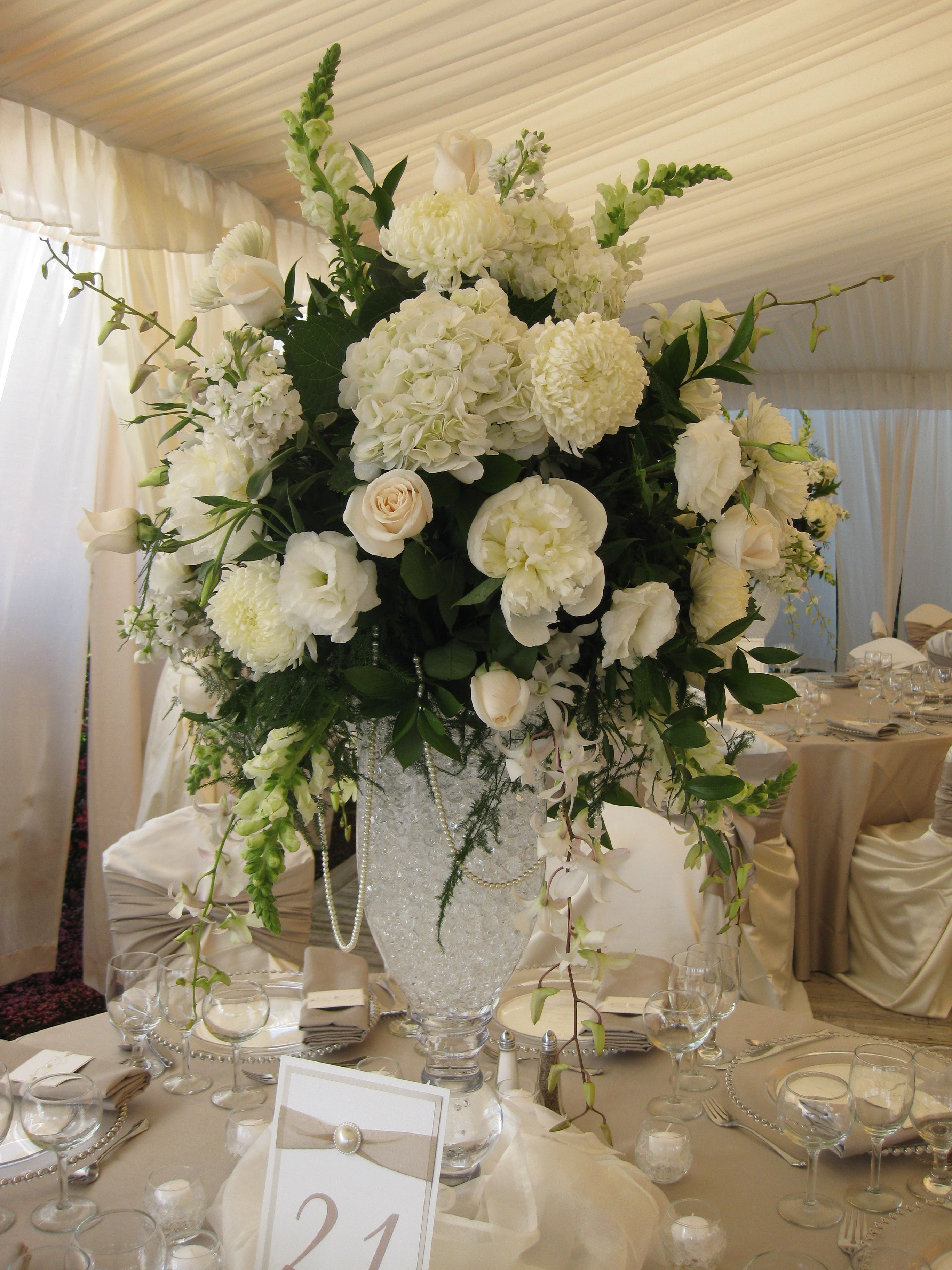 Tall centerpiece of all white and ivory flowers pearl