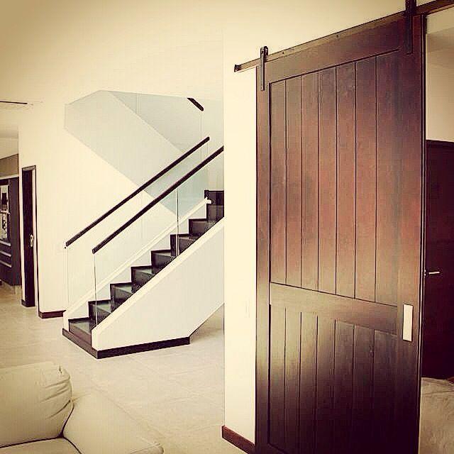 puerta corrediza madera lustrada rieles vistos escalera moderna de madera barandas de vidrio