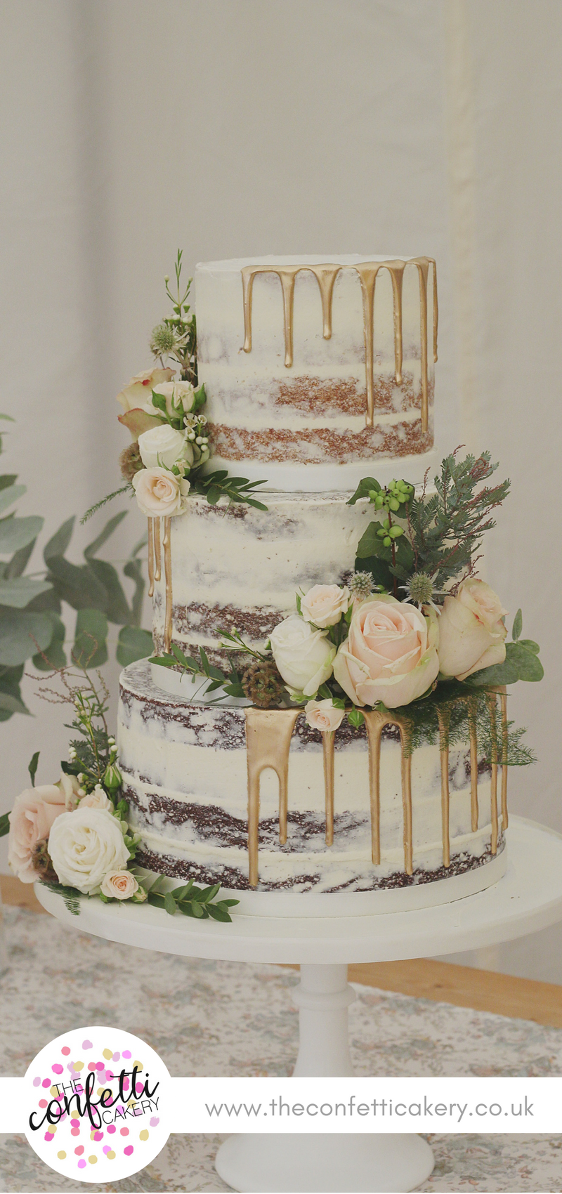 Semi-naked wedding cake with gold drips and fresh flower and foliage decoration….