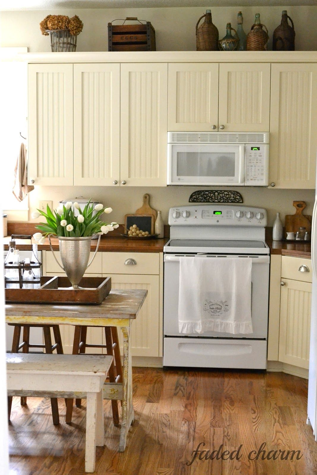 Faded charm love the beadboard cabinets do with green stove