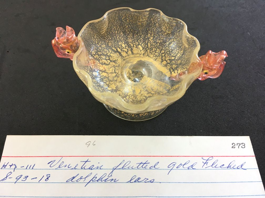 "Clear ruffled glass bowl on rounded pedestal base with gold flecks and pink dolphin handles. Each . 1 ½""T x 3""D. Hand blown, pontils unpolished."