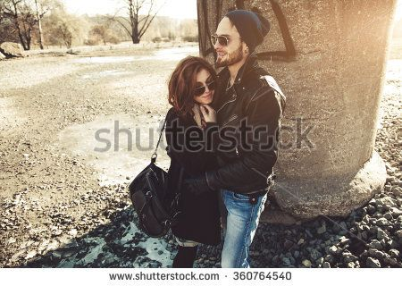 Cheerful and beautiful rock and roll couple walking outdoors on a sunny day