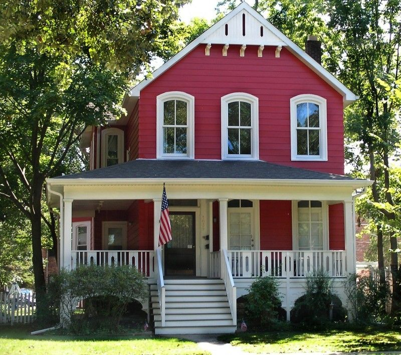 Red Farmhouse Exterior With White Framed Exterior Windows White Exterior Railing And St Red House Exterior Farmhouse Style House Plans Victorian Homes Exterior