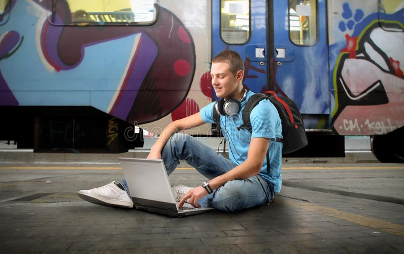 Elearning. Young man sitting on the platform of a train