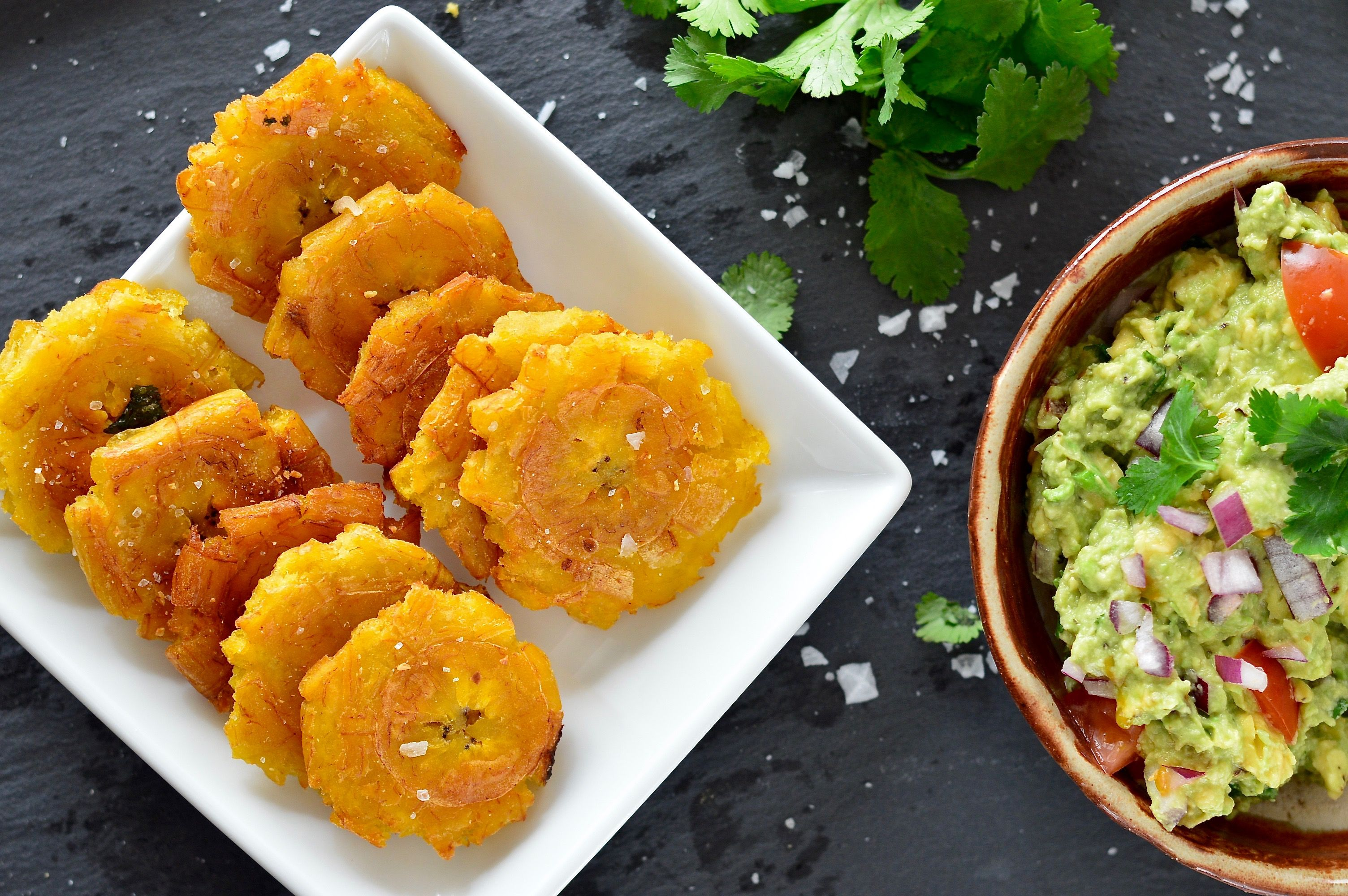 Tostones (Fried Green Plantains) are by far the best thing to happen since sliced bacon. Golden, brown, delicious, salty & crunchy...what more can you want?