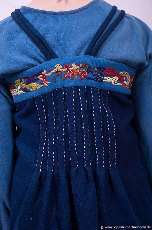 Kjersti Martinsdottir's Birka apron dress with open front and pleats in the back, rear view.  Note the Oseberg-inspired embroidery. (Site is in German)
