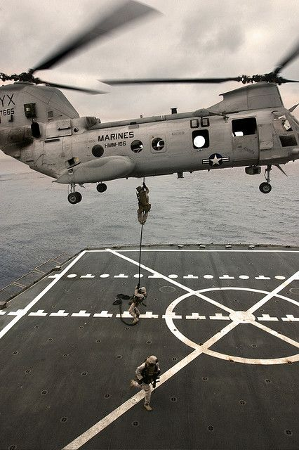 A CH-46E Sea Knight helicopter with Marine Medium Helicopter Squadron 166 hovers above USNS Yukon as Marines with the 11th Marine Expeditionary Unit fast-rope to the flight deck during a maritime boarding exercise July 30.