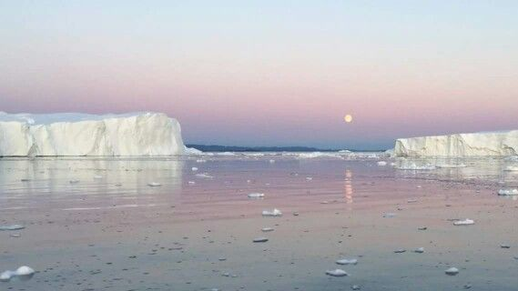 Full moon and midnight sun in Greenland