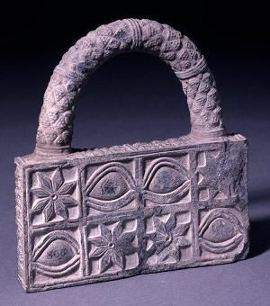 From Ur: Mystery Item.  Height: 21 centimetres (8.26 inches).  Width: 19.5 centimetres (7.67 inches).  Made of stone, it is decorated with the eye motif and the eight-pointed rosettes that were so meaningful to the Sumerians. The handle is similar to the kind found on a woven reed basket. The original purpose of the object isn't known.