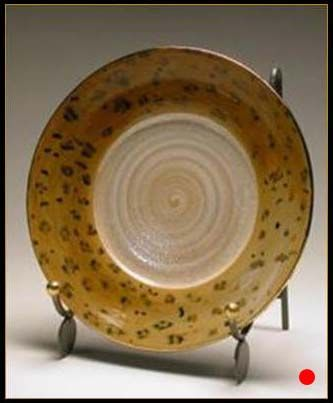 A thrown plate with gold lluster in leopard skin pattern.